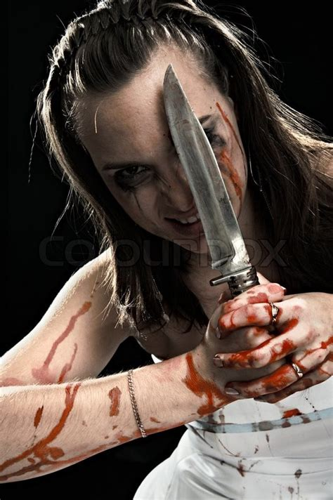 Woman with knife isolated on black