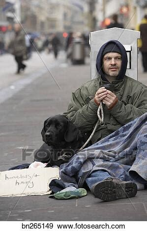 Stock Photograph of Homeless man with dog and sign